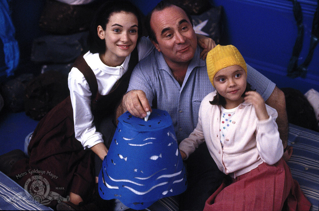two young girls with a father-figure in the middle holding a blue lampshade with fish cut out. they are all smiling.